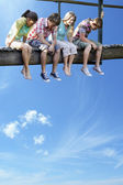 Teenagers sitting on wooden bridge — Stock Photo
