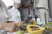 Chef peeling tropical fruit — Stock Photo