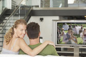 Woman with man watching movie on television — Stock Photo