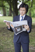 Businessman reading newspaper at park — Stock Photo