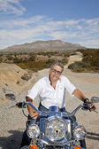 Senior man sits on motorcycle — Stock Photo
