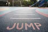 """Jump"" written into rubber floor — Stock Photo"