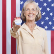 Woman with election badge against American flag — Stock Photo