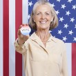 Woman with election badge against American flag — Stock Photo #33990221
