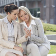 Businesswomen using mobile phone together — Stock Photo #33991327