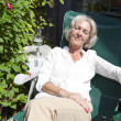Senior woman relaxing on lounge chair — Stock Photo #33992293