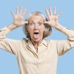 Senior woman making funny faces — Stock Photo