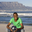 Young man with football on Table Mountain beach — Stock Photo #33993225
