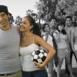 Couple holding soccer ball enjoying with friends — Stock Photo #33993263