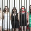Woman with female friends behinds prison bars — 图库照片