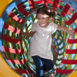 Girl climbs through netted tunnel — Stock Photo #33997853