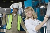 Woman checking newspaper with colleague — Stock Photo