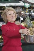 Woman weighing pineapple — Stock Photo