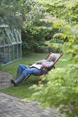 Gardener sleeps on deckchair in back garden — Stock Photo