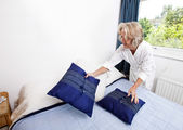 Woman setting up cushions on bed — Stock Photo