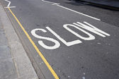 Road marking saying Slow — Stock Photo