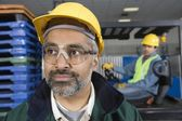 Serious man standing in factory — Stock Photo