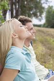 Woman  relaxing by man in forest — Stock Photo