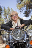 Senior woman leaning on motorcycle — Stock Photo