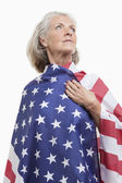 Senior woman wrapped in American flag — Stock Photo