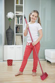 Girl sweeping floor — Stock Photo