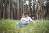 Man and girl sit in woodland clearing — Fotografia Stock