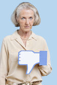 Senior woman with fake dislike butto — Stock Photo