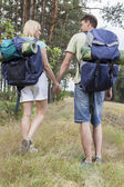 Backpackers holding hands in countryside — Stock Photo