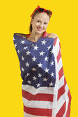 Woman wrapped in American flag — Stock Photo