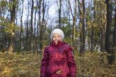 Girl standing under falling leaves — Stock Photo