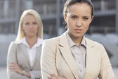 Serious young businesswoman with female colleague — Stock Photo