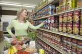 Woman selects tinned goods in supermarket aisle — Stock Photo