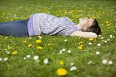 Pregnant woman lying on grass — Stock Photo