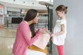 Mother giving daughter shopping bag — Foto de Stock