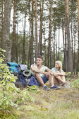 Hiking couple relaxing in forest — Stock Photo
