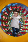 Girl climbs through netted tunnel — Stock Photo