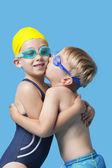 Young siblings in swimwear embracing — Stock Photo