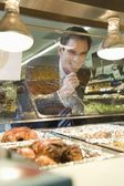 Man grins through glass of meat counter — Stock Photo