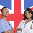 Male and female surgeons over British flag — Stock Photo