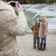 Mother taking photo of children — Stock Photo #34000461