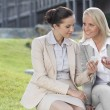 Businesswomen sitting against office building — Stock Photo #34000721