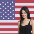 Woman smiling against American flag — Stock Photo