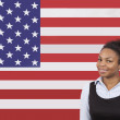 Businesswoman smiling over American flag — Stock Photo #34001815