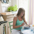Pregnant woman sitting at kitchen table eating breakfast — Stock Photo #34002041