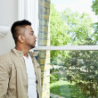 Indian man looking out window — Stock Photo #34002057