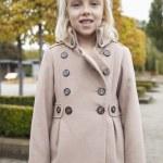 Girl in winter coat standing at park — Stock Photo #34002457