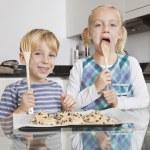 Boy with sister tasting spatula mix — Stock Photo #34002967