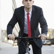 Businessman riding bicycle on street — Stock Photo #34004413