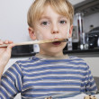 Boy tasting spatula mix — Stock Photo
