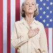 Senior woman against American flag — Photo